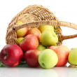 Stock Photo: Juicy apples with green leaves in basket, isolated on white