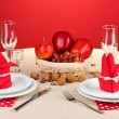 Table setting in red tones on color background — Stock Photo #18993773