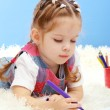 Cute little girl playing with multicolor pencils, on blue background — Stock Photo #18994159
