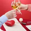 Hands of romantic couple toasting their wine glasses over a restaurant table — Stock Photo #18994681