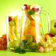 Jar and glass with citrus fruits and raspberries, on green background — Stock Photo