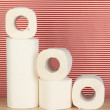 Rolls of toilet paper on striped red background — Stock Photo #18996751