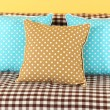 Colorful pillows on couch on yellow background — 图库照片