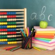 Toy abacus, books and pencils on table, on school desk background — Stock Photo #18997597