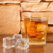 Glass of whiskey and ice on brick wall background — Stock Photo