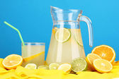 Citrus lemonade in glass and pitcher of citrus around on yellow fabric on blue background — Foto de Stock