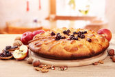 Tasty homemade pie with jam and apples, on wooden table in cafe — Stock Photo