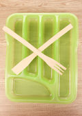 Green plastic cutlery tray with crossed wooden fork and scapula on wooden table — Stock Photo
