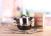 Composition of kitchen tools and cook book on table in kitchen — Stock Photo