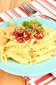 Plato de pasta rigatoni con salsa de tomate sobre mesa de madera de cerca — Foto de Stock