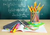 Retour à l'école - tableau noir avec équipement-plumier et école sur table — Photo