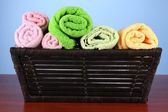 Colorful towels in basket on color background — Stock Photo
