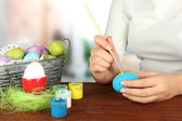 Young woman painting Easter eggs, on bright background — Stock Photo