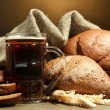 Tankard of kvass and rye breads with ears, on wooden table on brown background — Stock Photo #19022663