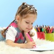 Stock Photo: Cute little girl playing with multicolor pencils, on blue background