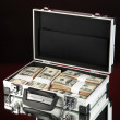 Suitcase with 100 dollar bills on dark color background — Stock Photo