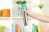 Sprayed air freshener in hand on white shelves background — Stock Photo