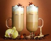 茶色の背景にスパイスとガラス カップで香りの良いコーヒー カフェラテ — ストック写真