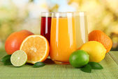 Glasses of juise with leafs and fruits on table on bright background — Stock Photo