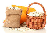 Pumpkin seeds in sack and wicker basket, isolated on white — Stock Photo