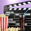 Movie clapperboard, cola and popcorn on purple background — Stockfoto