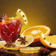 Fragrant mulled wine in glass with spices and oranges around on yellow background — Stock Photo