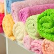 Colorful towels on shelves in bathroom — Stock Photo #19086721