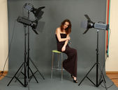 Beautiful professional female model resting between shots in photography studio shoot set-up — Stock Photo