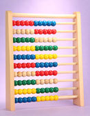 Bright wooden toy abacus, on purple background — Foto Stock