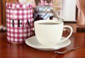 Jar and cup of tea on table in room — Stock Photo