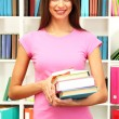 Young attractive female student holding her school books in library — Stock Photo #19135105
