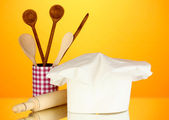 Chef's hat with spoons and battledore on orange background — Stock Photo