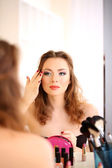 Young beautiful woman making make-up near mirror — Stok fotoğraf