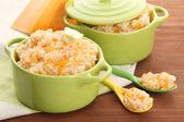 Taste rice porridge with pumpkin in saucepans on wooden background — Stockfoto