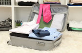 Open grey suitcase with clothing in room — Stock Photo