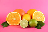 Fruits with leafs on pink background — Stock Photo