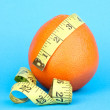 Orange with measuring tape on blue background — Stock Photo