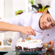 Young woman chef cooking cake in kitchen — Stock Photo #19159825