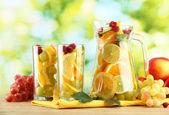 Džbán a sklenice s citrusových plodů a maliny, na zeleném pozadí — Stock fotografie