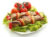 Tasty grilled meat and vegetables on skewers on plate, isolated on white — Stock Photo
