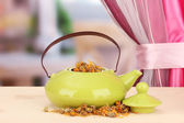 Dried herbs in teapot on wooden table, on bright background. Conceptual photo of herbal tea. — Stock Photo