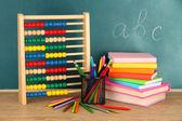 Spielzeug abakus, bücher und stifte auf tisch, mit der schule-schreibtisch-hintergrund — Stockfoto