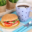 Appetizing sandwich on color plate on wooden table on window background — Stock Photo