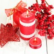 Royalty-Free Stock Photo: Red candle with christmas decoration on light background
