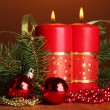 Two candles and christmas decorations, on brown background — Stock Photo #19163805
