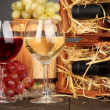 Stock Photo: Wooden case with wine bottles, barrel, wineglasses and grape on wooden table on grey background