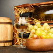 Stock Photo: Wooden case with wine bottles, barrel, wineglass and grape on wooden table on grey background