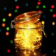 Christmas lights in glass bottle on blur lights background — Stock Photo #19164167