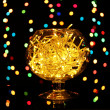 Christmas lights in glass bowl on blur lights background — Stock Photo #19164173