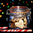 Tasty cookies in glass bottle on blur lights background — Stock Photo #19164183